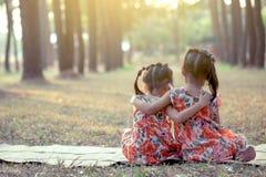 Achtereind van twee meisjes samen het zitten en omhelzing Stock Fotografie