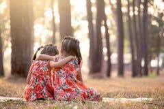 Achtereind van twee meisjes samen het zitten en omhelzing Stock Afbeeldingen