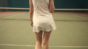 Achtereindlengte van een jonge sportieve sexy tennisspeler die naar het net in het behandelde hofgebied lopen Langzame Motie stock footage
