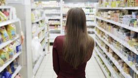 Achtereindmening, vrouw die bij de supermarkt winkelen, steadicam schot stock videobeelden