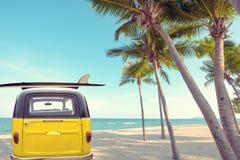 Achtergedeelte van uitstekende die auto op de tropische strandkust wordt geparkeerd met een surfplank op het dak royalty-vrije stock afbeelding