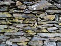 Achtergrond als muur van gestapelde donkergrijze, gespleten lei stock afbeelding