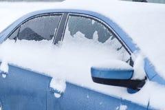 Achtergrond De blauwe auto op de straat in sneeuw stock foto's
