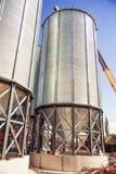 Achtergrond, de graanschuuren van metaalvaten op de hemelachtergrond stock foto