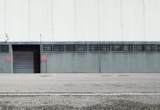 Achtergrond in de voorsteden Een asfaltweg voor een wit en grijs gebouw met een zwart rollend blind Prohibiti stock afbeelding