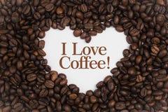 Achtergrond die van koffiebonen wordt gemaakt in een hartvorm met de Koffie van de bericht` I Liefde! ` Royalty-vrije Stock Foto's