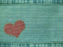 Achtergrond het hart in bijlage door draden aan jeans Stock Foto