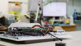 Achtergrond met de mensenwerken in het elektronische centrum van de reparatiedienst in workshop stock videobeelden