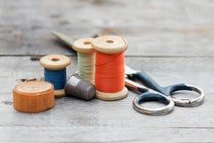 Achtergrond met het naaien van hulpmiddelen en gekleurde draad Stock Fotografie