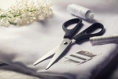 Achtergrond met het naaien van hulpmiddelen Schaar, spoelen met draad en naalden en textiel op witte lijst Stock Foto's