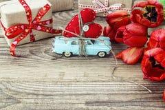 Achtergrond met miniatuur blauwe stuk speelgoed auto die een hart en een rood dragen Stock Foto
