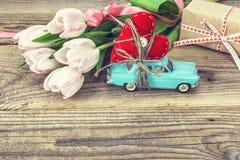 Achtergrond met miniatuur blauwe stuk speelgoed auto die een hart en een roze dragen Royalty-vrije Stock Foto
