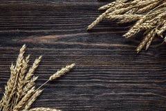 Achtergrond met oren van tarwe op de donkere houten raad Stock Foto