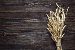 Achtergrond met oren van tarwe op de donkere houten raad Stock Foto's