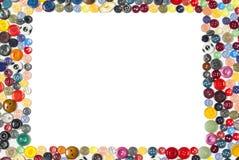 Achtergrond met rechthoekig kader - multicolored knopen op een witte oppervlakte stock foto