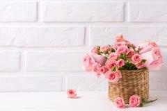 Achtergrond met roze rozenbloemen tegen witte bakstenen muur stock afbeelding