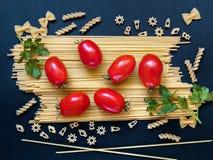 Achtergrond met spaghetti, tomaten en greens op een donkere backgro Royalty-vrije Stock Foto