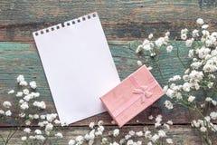 Achtergrond met witte kleine bloemen, lege blocnotepagina en gift Royalty-vrije Stock Fotografie
