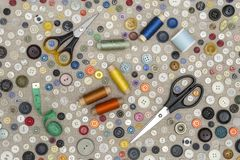 Achtergrond - multicolored knopen en naaiende toebehoren op de stof stock afbeelding