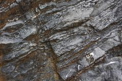 Achtergrond op basis van de textuur van rots Zwarte en bruine steen met het hellen lagen en barsten stock fotografie