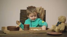 Achtergrond Smakelijke pizza Weinig jongen die een plak van pizza hebben Hongerig kind die een beet van pizza nemen Concept voedi stock footage