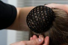 Achtergrond stilistkapper verzameld lang haar in een strak broodje vast met zwarte netwerk en steken met zwarte metaalnagels stock foto