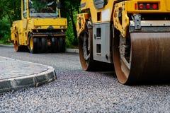 Achtergrond van asfaltrol dat stapelt en heet asfalt drukt De machine van de wegreparatie royalty-vrije stock afbeeldingen