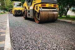 Achtergrond van asfaltrol dat stapelt en heet asfalt drukt De machine van de wegreparatie royalty-vrije stock foto