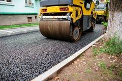 Achtergrond van asfaltrol dat stapelt en heet asfalt drukt De machine van de wegreparatie stock afbeeldingen