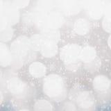 Achtergrond van Bokeh van Defocused de zilveren en witte Kerstmis met snowf Royalty-vrije Stock Afbeeldingen