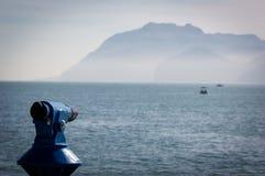 Achtergrond van een blauwe panoramische toeristische telescoop die het overzees met een boot overzien stock fotografie