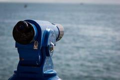 Achtergrond van een blauwe panoramische toeristische telescoop die het overzees overzien stock afbeelding