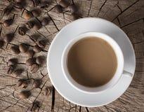Achtergrond van een kleine kop hete koffie met melk en een aantal onderliggende gehele koffiebonen op een verbroken stomp Stock Afbeeldingen