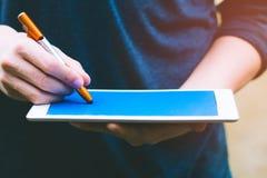 Achtergrond van financiële planning en investering concept Jonge mensenholding en het schrijven op lege het scherm digitale table stock foto's