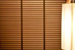 Achtergrond van houten vensterzonneblinden, zonneschijn en schaduw op blind venster stock fotografie