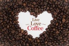 Achtergrond van koffiebonen wordt gemaakt in een hartvorm met bericht ` Live Love Coffee ` die Royalty-vrije Stock Afbeeldingen