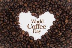 Achtergrond van koffiebonen wordt gemaakt in een hartvorm met de Koffie van de bericht` Wereld Dag ` die Royalty-vrije Stock Foto's