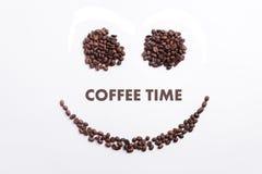 Achtergrond van koffiebonen wordt gemaakt in een vorm van het smileygezicht met de tijd ` die van de bericht` Koffie Stock Afbeelding