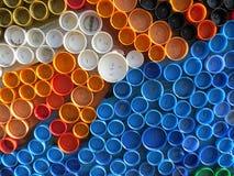 Achtergrond van plastic kleurrijke kroonkurken Verontreiniging met plastic afval Milieu en ecologisch evenwicht Kunst van troep stock fotografie