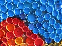 Achtergrond van plastic kleurrijke kroonkurken Verontreiniging met plastic afval Milieu en ecologisch evenwicht Kunst van troep stock foto's