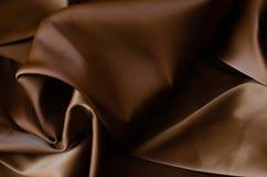 Achtergrond van satijnstof van bruine kleur royalty-vrije stock afbeeldingen