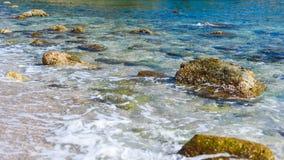 Achtergrond van transparante zeewater en bodem, met stenen en golven stock afbeelding