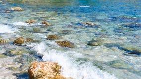 Achtergrond van transparante zeewater en bodem, met stenen en golven royalty-vrije stock foto