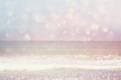 Achtergrond van vaag strand, overzeese golven en varende boot bij horizon met bokehlichten, uitstekende filter Royalty-vrije Stock Foto's