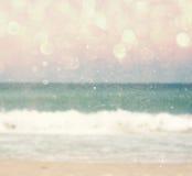 Achtergrond van vage strand en overzeese golven met bokehlichten, uitstekende filter stock foto