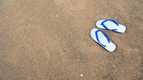 Achtergrond van witte pantoffels of wipschakelaars op strand Royalty-vrije Stock Foto