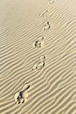 Achtergrond van zandrimpelingen bij het strand met drukken van voeten Royalty-vrije Stock Foto