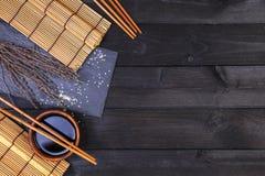 Achtergrond voor sushi Bamboemat en sojasaus op zwarte houten lijst Hoogste mening met exemplaarruimte royalty-vrije stock fotografie