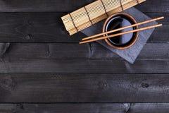 Achtergrond voor sushi Bamboemat, sojasaus, eetstokjes op donkere lijst stock afbeelding