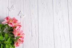 Achtergrond voor tekstbanner op een lichte houten achtergrond met roze bloemen en vlinders Spatie, kader voor tekst De kaart van  royalty-vrije stock foto